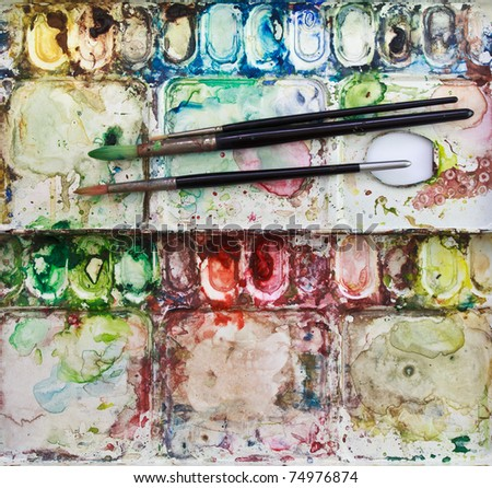 Paintbrushes on watercolor's metallic palette