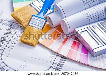 paintbrushes rolled blueprints calculator on color palette - stock photo