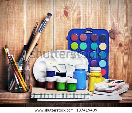 Paintbrushes, watercolor, gouache and paper are on wooden shelf