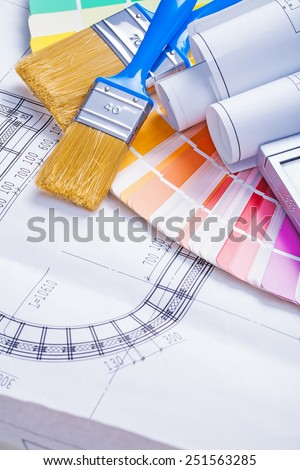 paintbrushes with blue handles and rolled blueprints on color palette  - stock photo