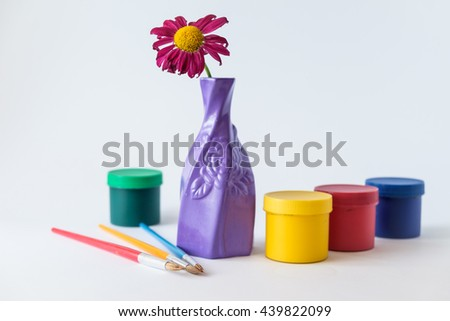 paintbrushes with liquid paint containers on foreground and flower in vase on white background  - stock photo