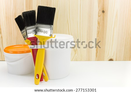 paintbrushes with two paint cans against wooden boards - stock photo