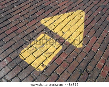 Painted arrow on brick road - stock photo