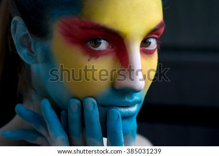 Painted beautiful woman face, artistic make up, body and face art, close up. Facial expression, emotions. Bird Halloween  beauty fashion style in red, yellow, blue colors. Halloween - stock photo