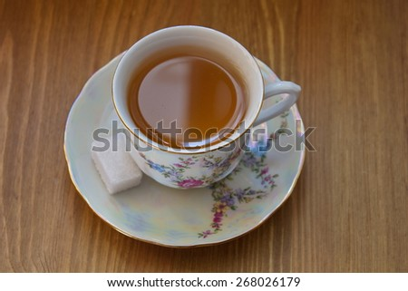 painted china tea cup with pattern of flowers, with cubes of sugar - stock photo