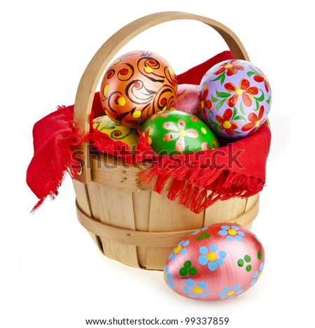 Painted colorful easter eggs in wooden basket , isolated on white