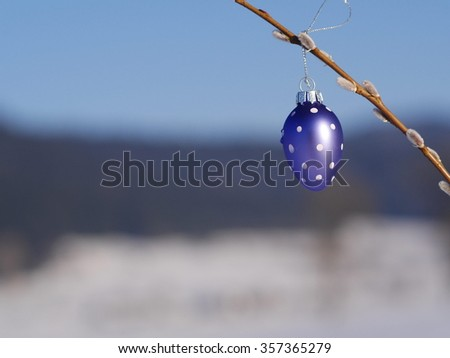 Painted Easter egg hanging on kittens tree branches on background of blue sky. Nice spring decoration. - stock photo