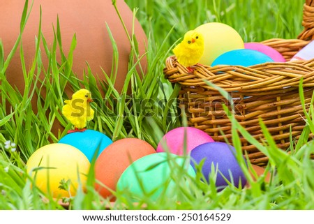 Painted Easter eggs and toy chickens on the background of a clay pitcher, wicker basket and green spring grass - stock photo