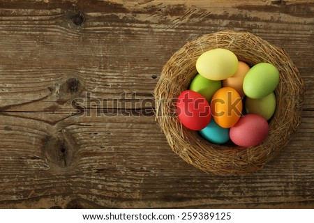 Painted Easter eggs basket on wooden background - stock photo