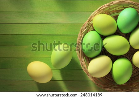 Painted Easter eggs basket on wooden background/ top view - stock photo
