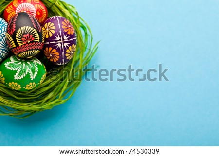 Painted easter eggs in basket on blue background - stock photo