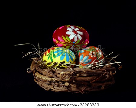 Painted Easter eggs in bird's nest over black background