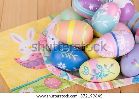Painted Easter eggs on a colorful plate - stock photo