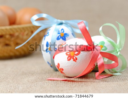 Painted easter eggs on canvas with the wicker basket as background