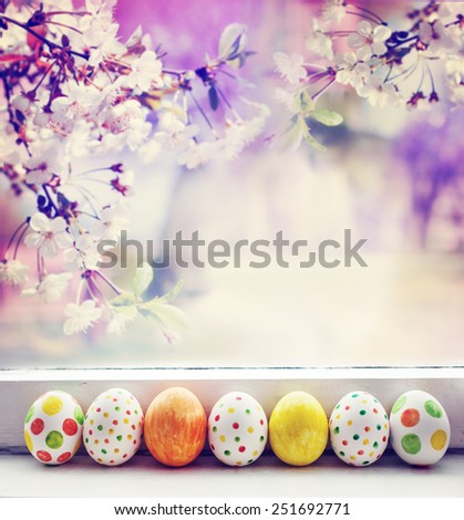Painted Easter Eggs over spring garden background / Easter holidays background - stock photo