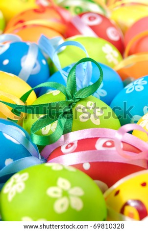 Painted easter eggs with bows uniform background - stock photo