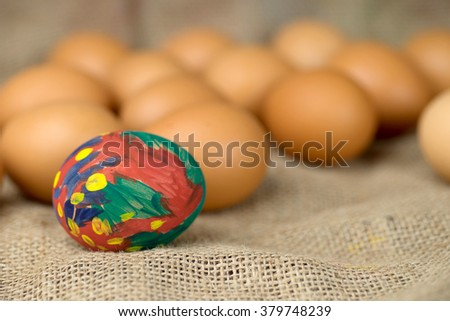painted egg on burlap cloth and colorful background for easter day