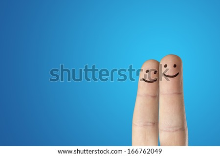 Painted finger smiley on blue background - stock photo