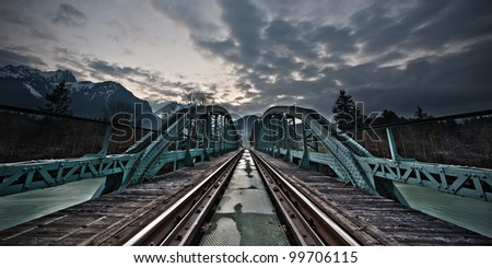 painted framework bridge and rails at sunset with dramatic cloudy sky