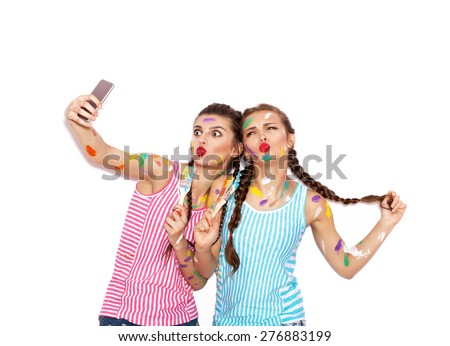 Painted girl friends having fun. Women with paintbrush taking selfie. White background not isolated - stock photo