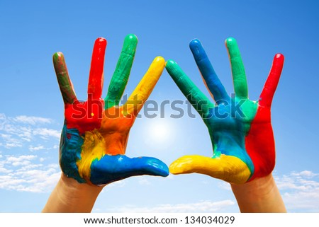Painted hands, colorful fun. Creative, funny and artistic means happy! Blue sky background - stock photo