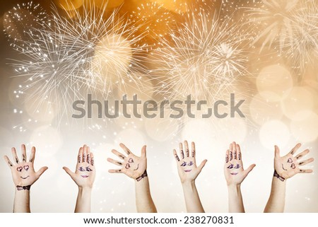 Painted hands with smiling faces celebrating New Year - New Year concept - stock photo