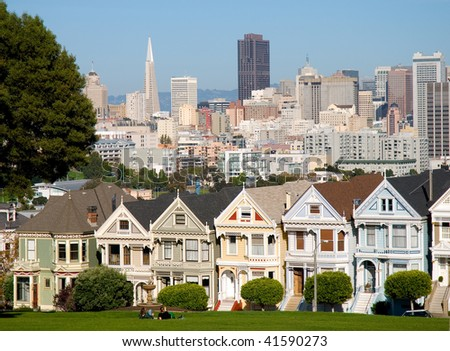 Painted Ladies Victorian houses, Alamo Square, San Francisco, California. The Transamerica building and other skyscrapers in the downtown area can be seen in the background - stock photo