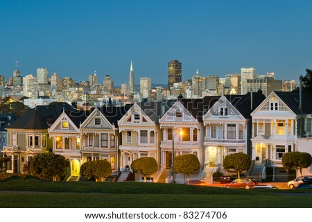 Painted Ladies with San Francisco skyline in the background as seen from Alamo Square with city lights - stock photo