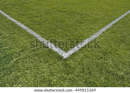Painted lines in the corner of a green grass playing field.