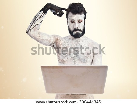 Painted man with laptop over ocher background - stock photo
