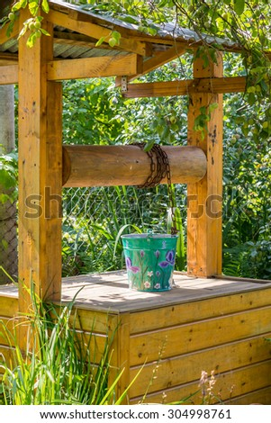 painted metal bucket on a wooden village well - stock photo