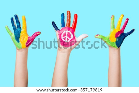Painted peace sign in girl's hand against war.