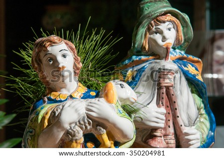 Painted pottery statue portraying a shepherd and his little sheep of a ceramic nativity scene by an artisan in Caltagirone - stock photo