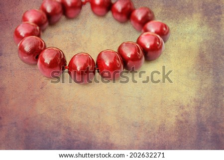 Painted red wooden beads on a grunge background