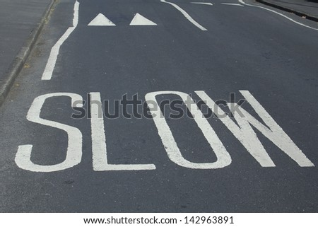 painted road warning saying 'slow' and speed bumps - stock photo