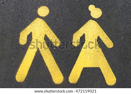 Painted sign on asphalt for pedestrian lane - man and woman