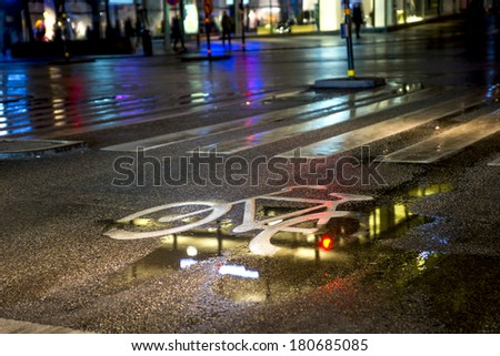 painted symbol in bicycle lane on wet street - stock photo
