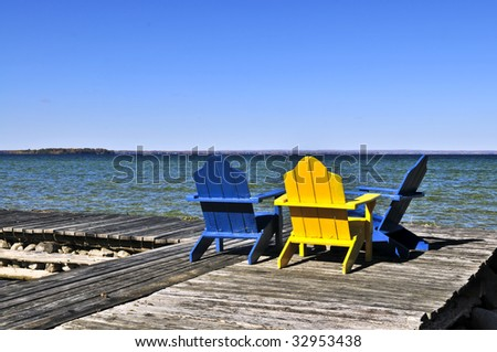 Painted wooden chairs on dock at a lake - stock photo
