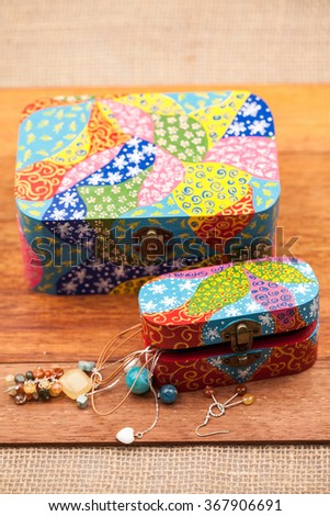 Painted, wooden small boxes for multiple purposes and jewels on a wooden surface
