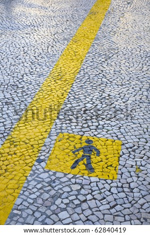 Painted yellow walk line, in the stone floor of an urban city, Lisbon, Portugal - stock photo