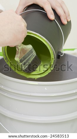 painter brushing in the paint in a bucket - stock photo