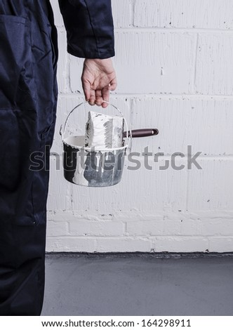 Painter / decorator holding paint bucket with brush in front of painted wall portrait - stock photo