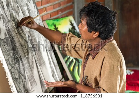 Painter drawing on easel in gallery, Bali, Indonesia - stock photo