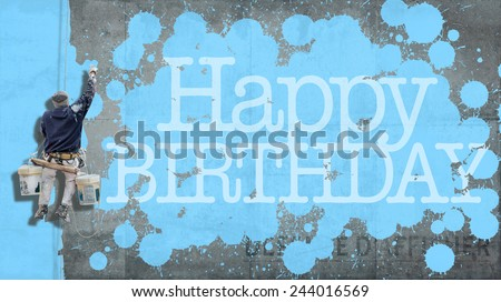 Painter hanging from harness painting a wall with the word Happy Birthday in blue - stock photo