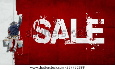 Painter hanging from harness painting a wall with the word sale - stock photo