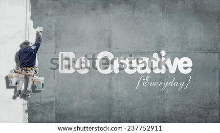 Painter hanging from harness painting a wall with the words be creative everyday - stock photo