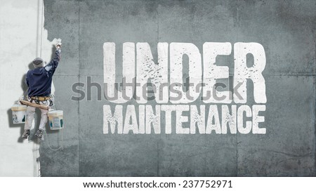 Painter hanging from harness painting a wall with the words Under Maintenance - stock photo