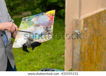 Painter holding a colorful palette and a paintbrush mixing colors in front of a sketchbook during an art class in a park - stock photo