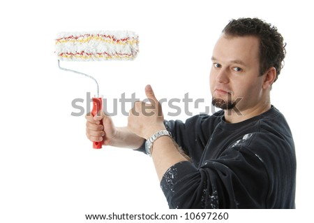 Painter holding a paint roller and thumb up - stock photo