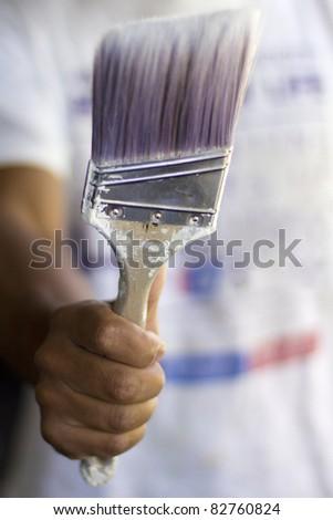 Painter holding his favorite paint brush. - stock photo
